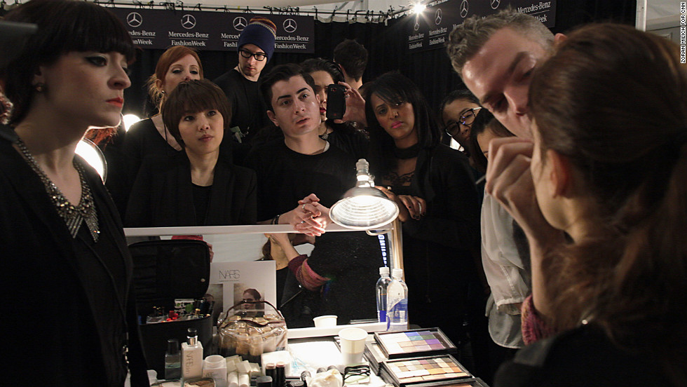 A model has her makeup done before a show February 8.