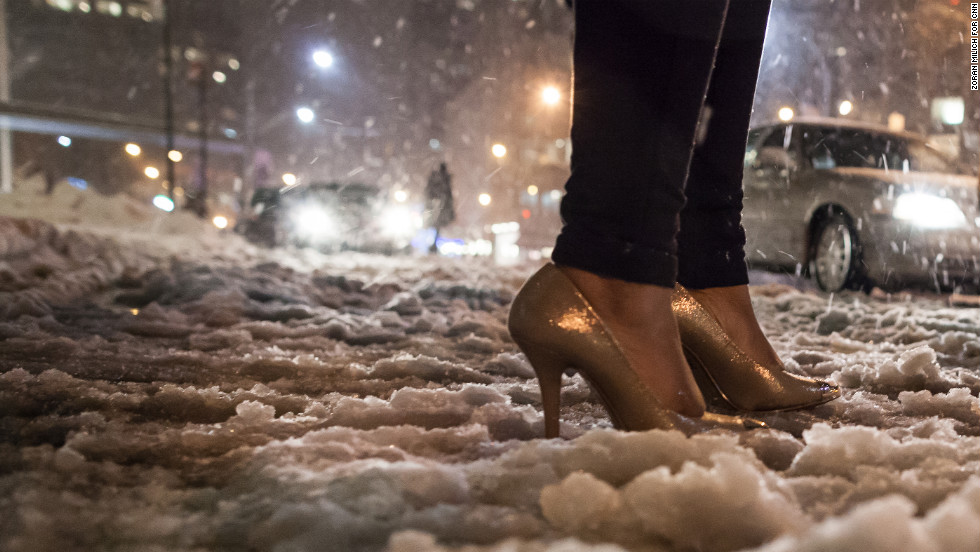 A fashion week attendee makes her way through the snow in high-heeled shoes on Friday.