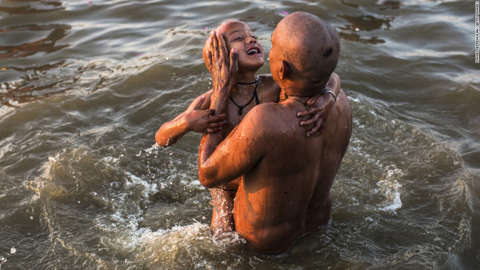 A father lifts his son out of the waters of the Sangam on Friday, February 8.