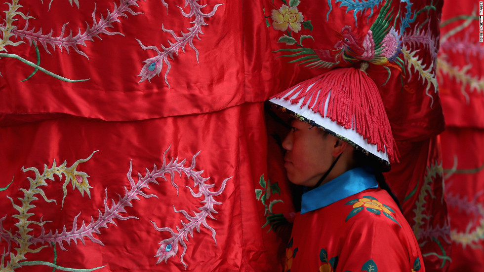 A Chinese paramilitary police officer dressed as a Qing Dynasty servant prepares for a re-enactment of an ancient ceremony on February 9.