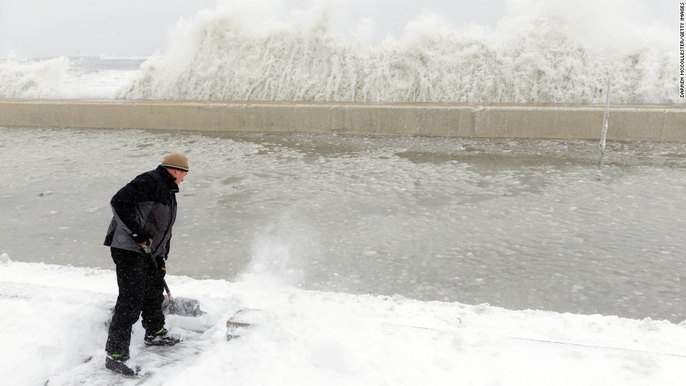 Mike Streeter shovels snow in his front yard as ocean water crashes over the sea wall just feet away on February 9 in Winthrop, Massachusetts.