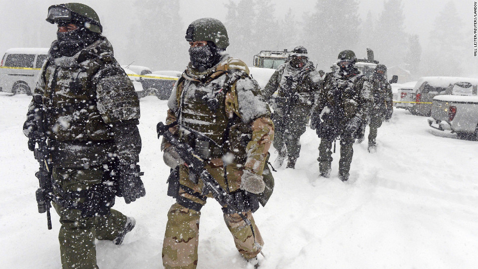 San Bernardino County Sheriff SWAT team members return to the command post at Bear Mountain in Big Bear Lake, California, on Friday, February 8, after heavy snow hindered the manhunt for ex-LAPD cop Christopher Jordan Dorner.