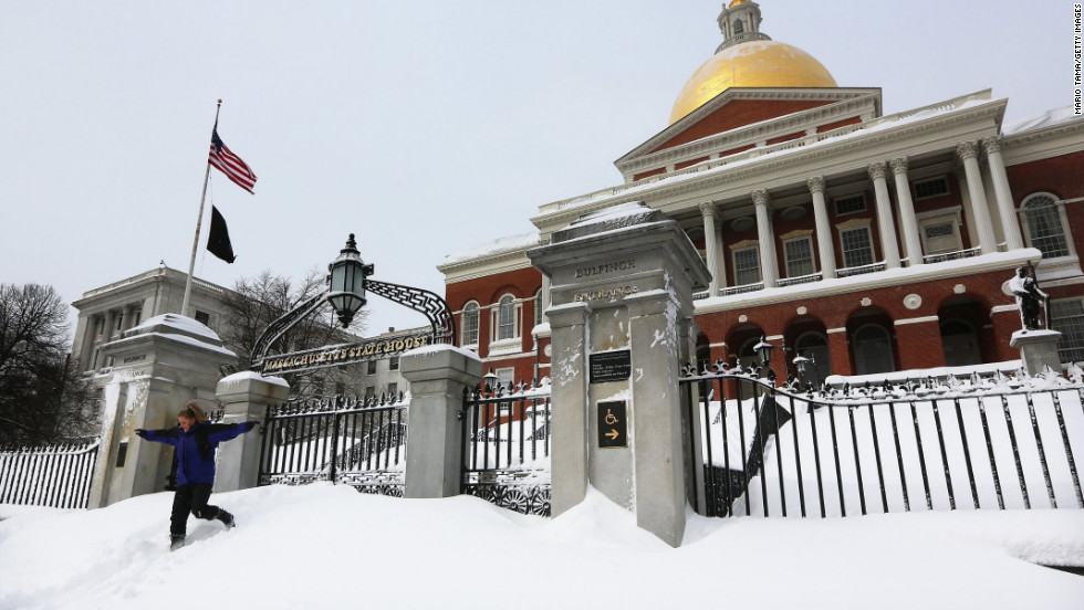 A young woman jumps down from snow piled in front of the Massachusetts State House after posing for a photo in Boston on Saturday.