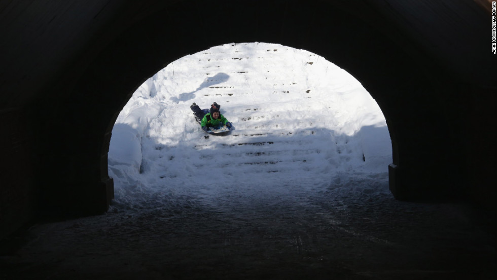 A child tubes down snow-covered stairs in Central Park on Saturday.
