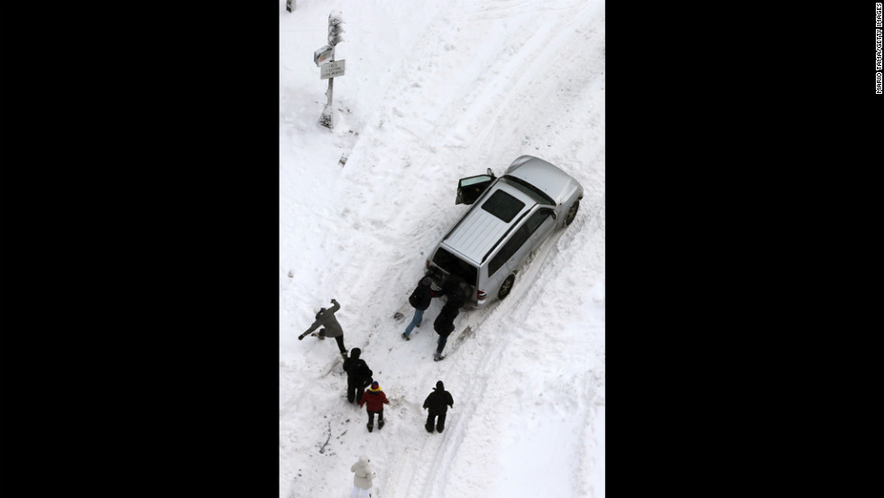 People attempt to push a stuck vehicle in the Back Bay neighborhood of Boston on Saturday.