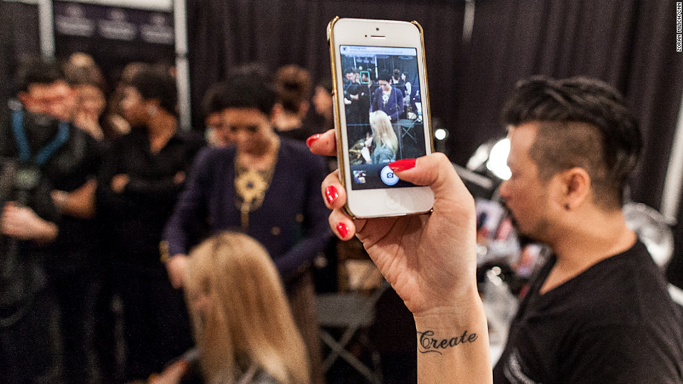 A woman takes a photo of teams and models backstage at the Tracy Reese show February 10.
