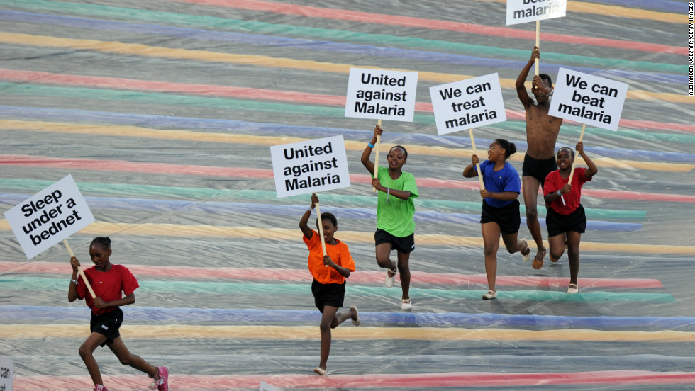 Children run with advertising banners highlighting the fight against malaria during a ceremony held ahead of the final.