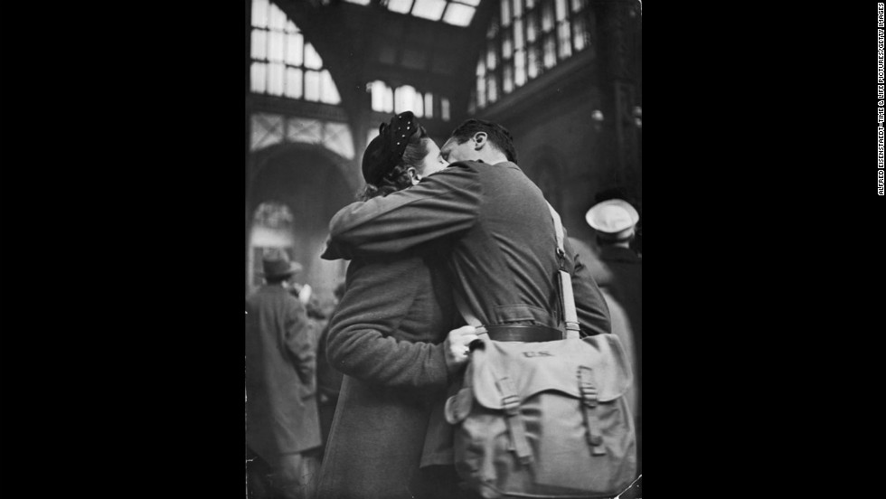 A soldier wraps his arms around his lover as they bid farewell.