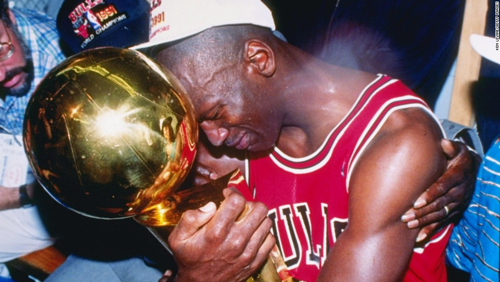 Michael Jordan of the Chicago Bulls hugs the NBA Championship Trophy after the Bulls defeated the Los Angeles Lakers 4 games to 1 to win the NBA Finals on June 12, 1991, at the Great Western Forum in Inglewood, California.