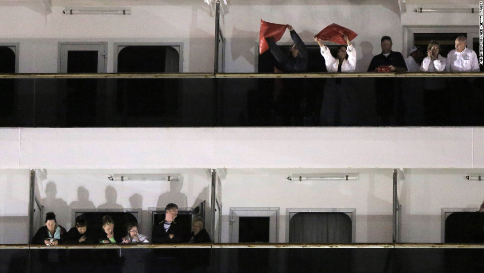 Passengers wave from the decks of the Triumph after docking at the Alabama Cruise Terminal in Mobile.