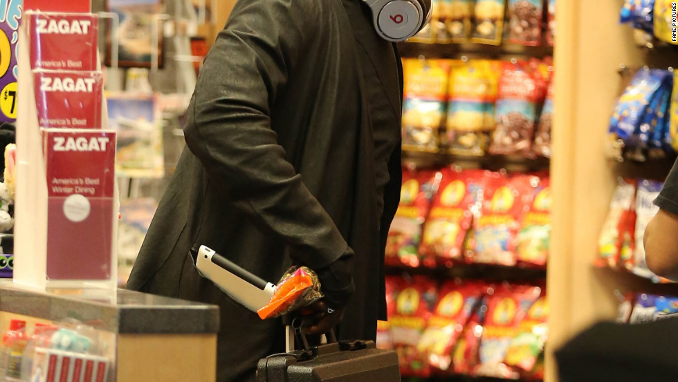 Will.i.am buys a few things at the airport.