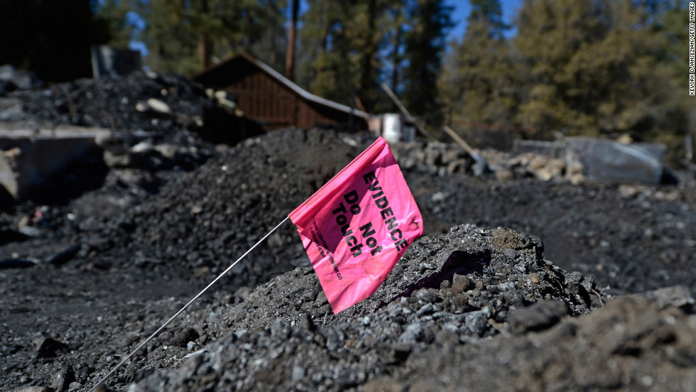 An evidence flag placed by San Bernardino County Sheriff's crime scene investigators sits on pile of rubble in the burned cabin on February 15.