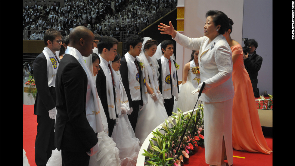 "Hak Ja Han Moon, right, the widow of the late Unification Church founder Sun Myung Moon, sprinkles the church's holy water onto newly married couples. This was the first Cosmic Blessing since the death of Sun Myung Moon, who <a href=""http://www.cnn.com/2012/09/02/world/asia/south-korea-reverend-moon-dead"" target=""_blank"">passed away in September 2012</a>."