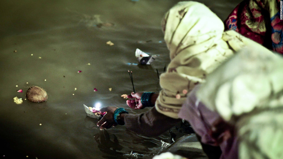 A woman places a floating candle on the Sangam on Sunday, February 17.