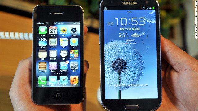 An employee of a mobile phone shop in Seoul, South Korea, holds up the Apple iPhone and a competitor, the Samsung Galaxy.