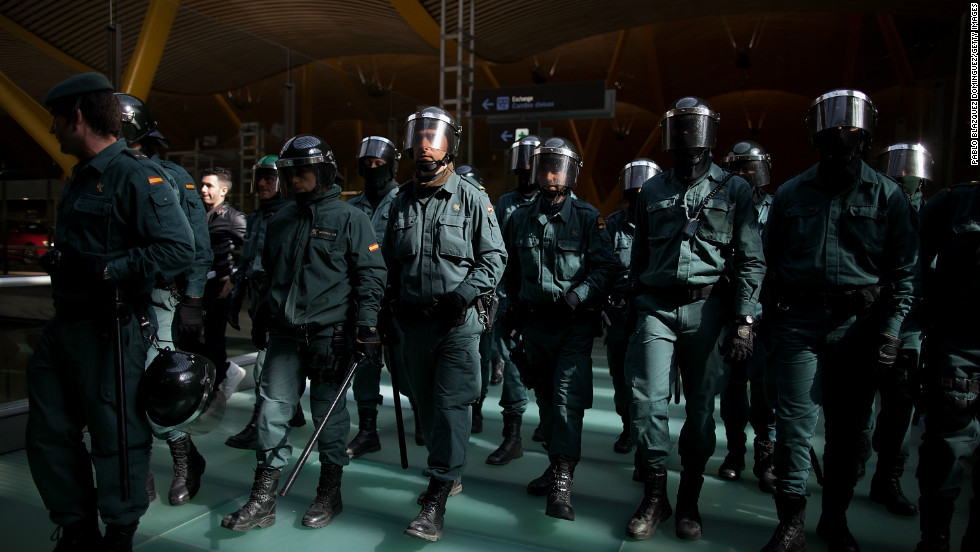 Riot Police walk forward making a cordon during a protest of Spanish Airline Iberia staff.