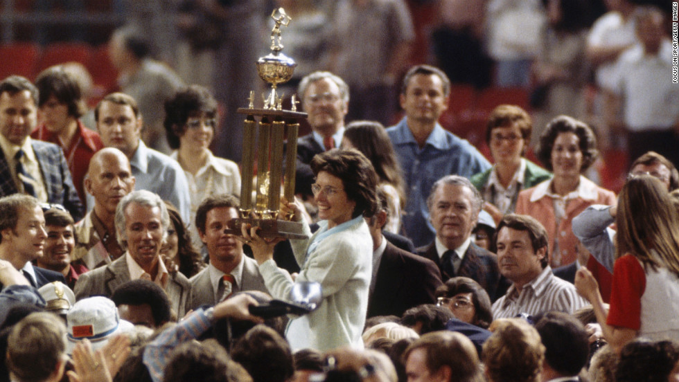 Billie Jean King holds up her trophy after defeating Bobby Riggs during the Battle of the Sexes tennis match in Houston on September 20, 1973. She became the first woman to beat a man in a professional tennis match.