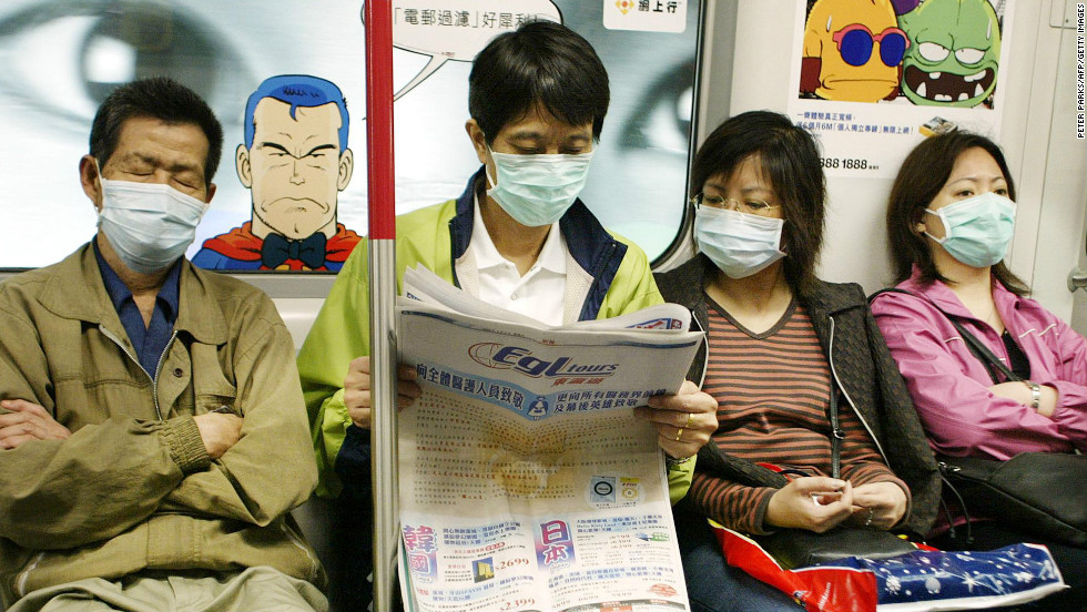 Subway passengers wear masks to protect against SARS on Hong Kong's MTR, April 4, 2003.