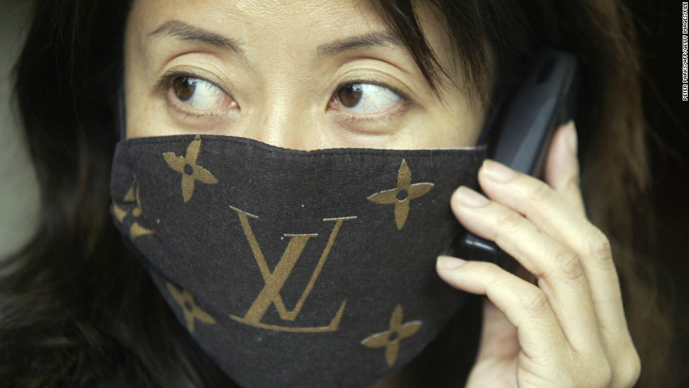 "A woman wears a mask with ""Louis Vuitton"" branding to protect against SARS, April 3, 2003."