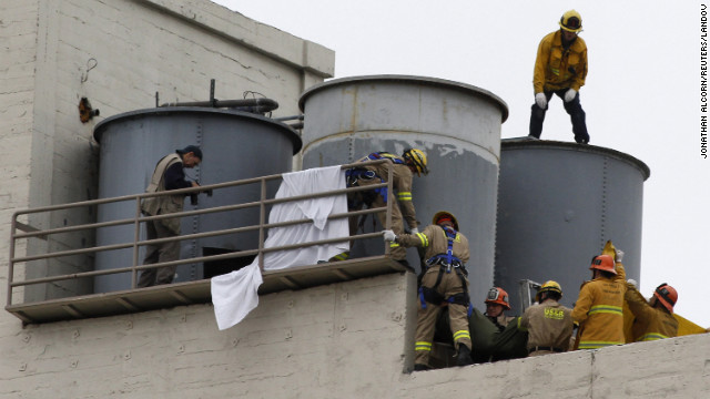 Image #: 21284029    Firefighters work to remove a body found inside a water tank on the rooftop of Hotel Cecil in Los Angeles, California February 19, 2013. Police were trying to determine on Tuesday if a body found in a water tank on top of a Los Angeles hotel is that of a 21-year-old Canadian woman who went missing while staying there more than two weeks ago. Elisa Lam, a student from Vancouver, British Columbia who was visiting Southern California on her own, was last seen at the Cecil Hotel in downtown Los Angeles on January 31 and authorities had characterized her disappearance as suspicious. REUTERS/Jonathan Alcorn (UNITED STATES - Tags: CRIME LAW CIVIL UNREST)       REUTERS /JONATHAN ALCORN /LANDOV