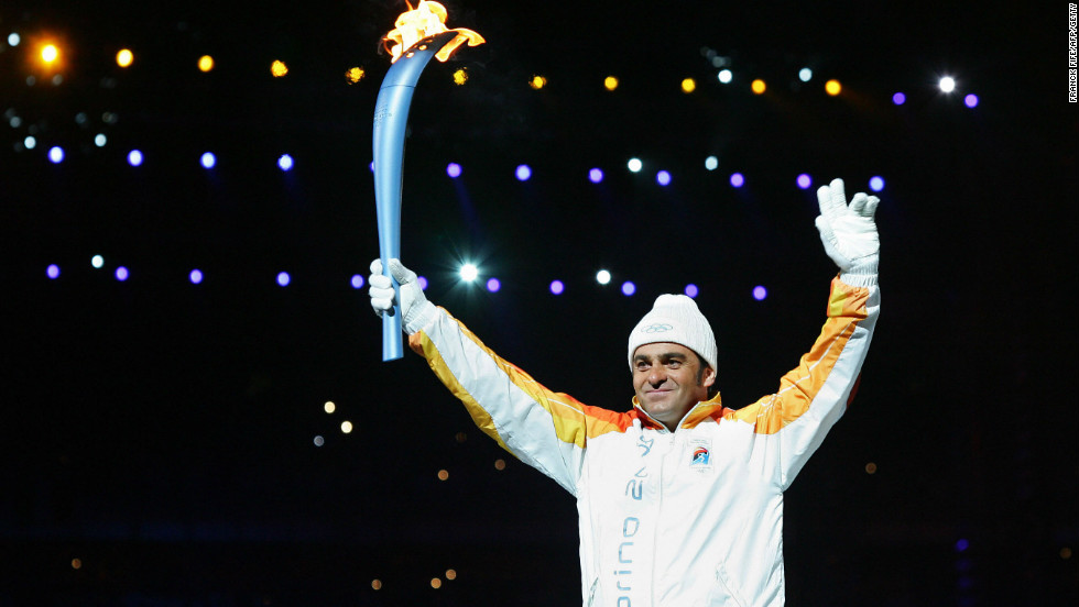 Tomba carries the Olympic torch into the stadium at the opening ceremony for the 2006 Winter Games in Turin.