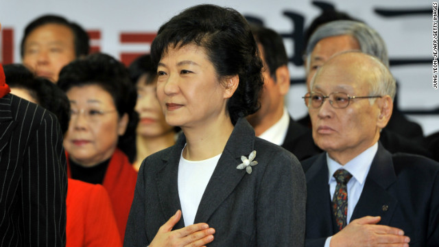 South Korea's president-elect Park Geun-Hye (L) from the ruling New Frontier Party salutes the national flag during a ceremony to disband her election camp at the party's headquarters in Seoul on December 20, 2012. South Korea elected its first woman president on December 19 with voters handing a slim but historic victory to conservative candidate Park Geun-Hye, daughter of the country's former military ruler.