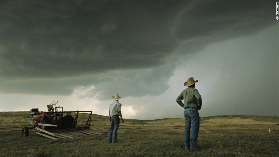 "The ""Greatest Photographs of the American West"" exhibit is currently touring the United States. Here, workers in Nebraska halt haying to watch as afternoon thunderheads fill the sky."