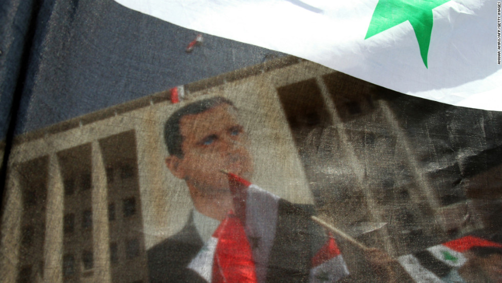 Syrians wave their national flag and hold portraits of al-Assad during a rally to show their support for their leader in Damascus on March 29, 2011.