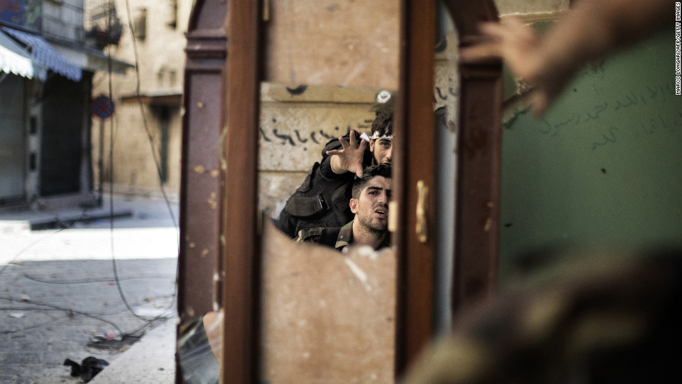 Free Syria Army fighters are reflected in a mirror they use to see a Syrian Army post only 50 meters away in Aleppo on September 16, 2012.