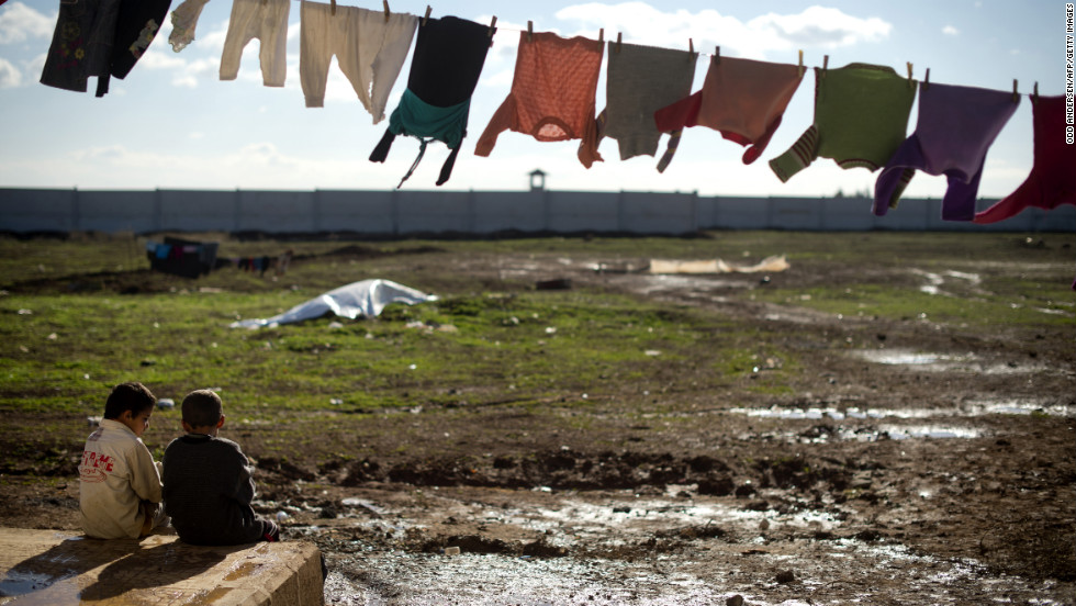 Two young boys sit underneath a washline in a refugee camp on the border between Syria and Turkey near Azaz on December 5, 2012.