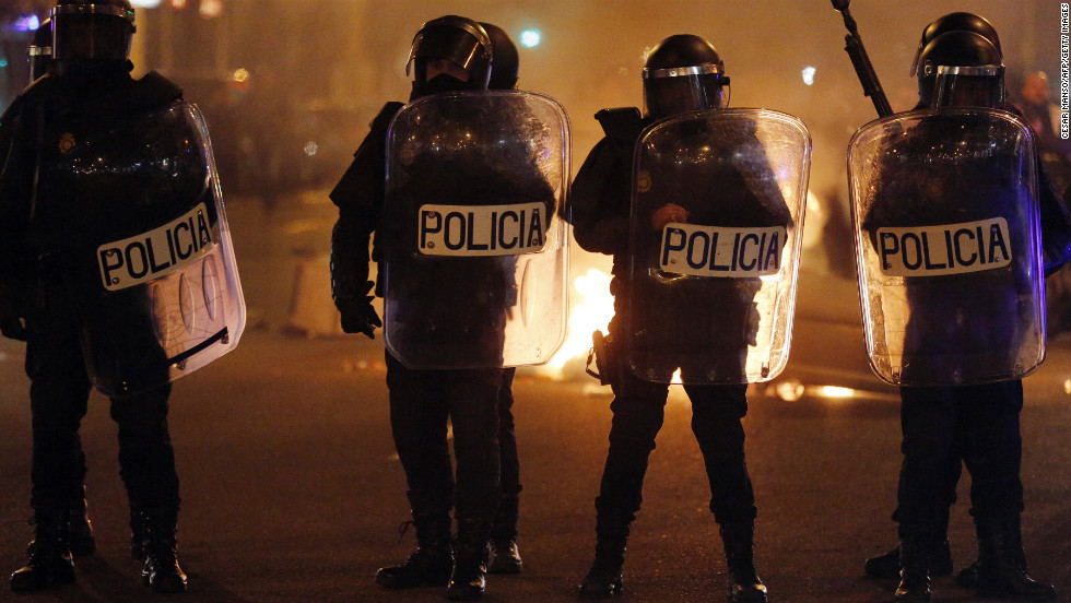 Spanish riot police stand in front of a fire at the end of a demonstration against government austerity measures in Madrid.