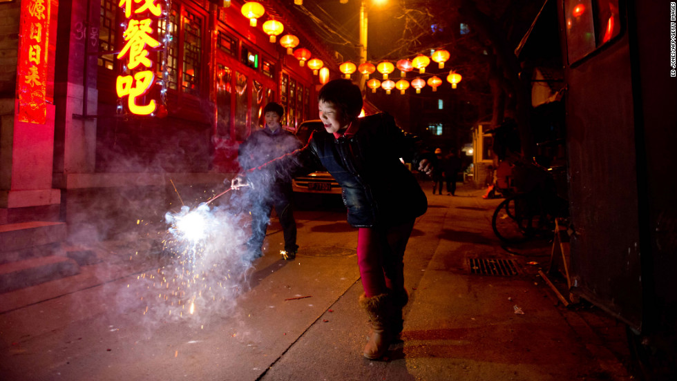A girl holds a firecracker in Beijing during the Lantern Festival on February 24.