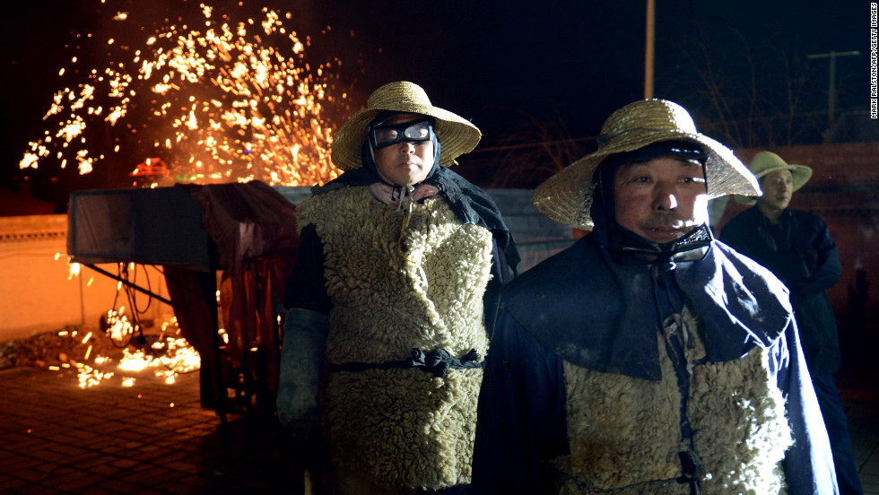 Chinese blacksmiths wait their turn to throw the molten metal against a wall in Nuanquan, on February 24.