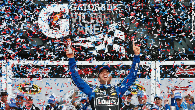 Jimmie Johnson raises his arms in victory after winning the NASCAR Sprint Cup Series Daytona 500 on Sunday, February 24, in Daytona Beach, Florida.