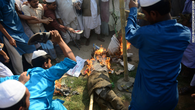 Protesters in Dhaka beat and burn an effigy of a blogger during a nationwide strike Sunday in Bangladesh.