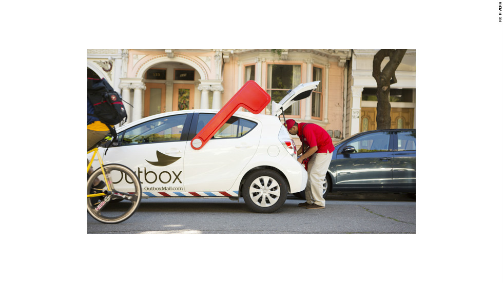 A bike messenger passes the Outbox Prius. The company is considering expanding to other forms of transportation, such as scooters.