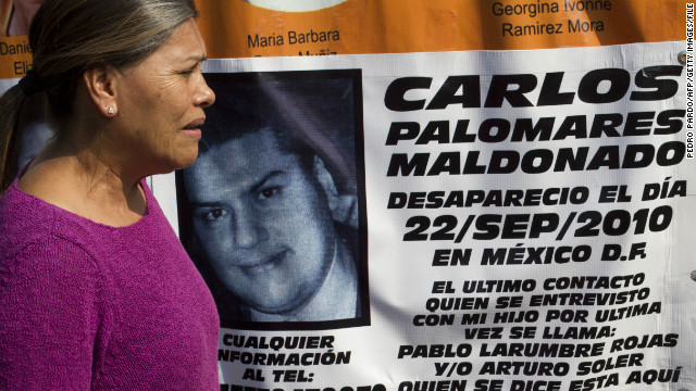 Ana Maria Maldonado stands by a banner for her missing son during a protestlast November in Mexico City.