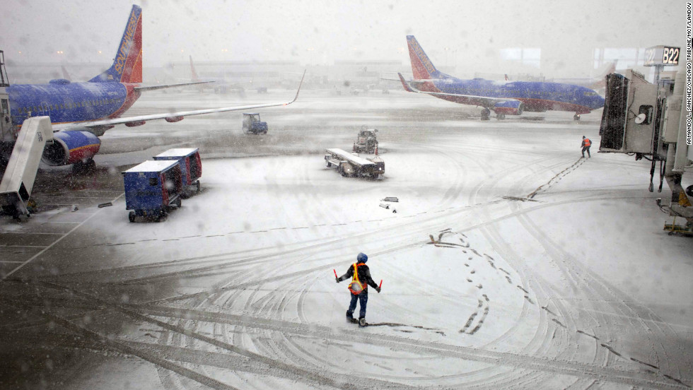 "Southwest Airlines employees guide a plane into the gate at Midway International Airport in Chicago on Tuesday, February 26. Back-to-back storms have hit the Great Plains, which is still digging out from last week's weather. <em>Are you experiencing the storm? If it's safe, <a href=""http://ireport.cnn.com/topics/877827""><em></em>share your photos</a></em>."