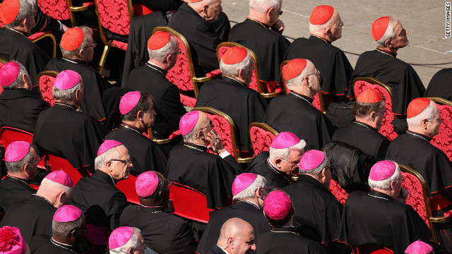 Archbishops (purple hats) and cardinals (red hats) sit in St Peter's Square on February 27 in Vatican City.
