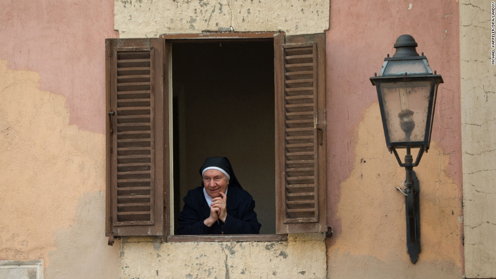 A nun looks out from the Apostolic Palace in Castel Gandolfo.