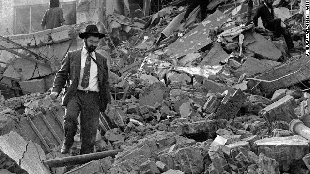 (File photo) A man walks over the rubble after a bomb exploded at the Israeli Mutual Association in Buenos Aires, 18 July 1994.
