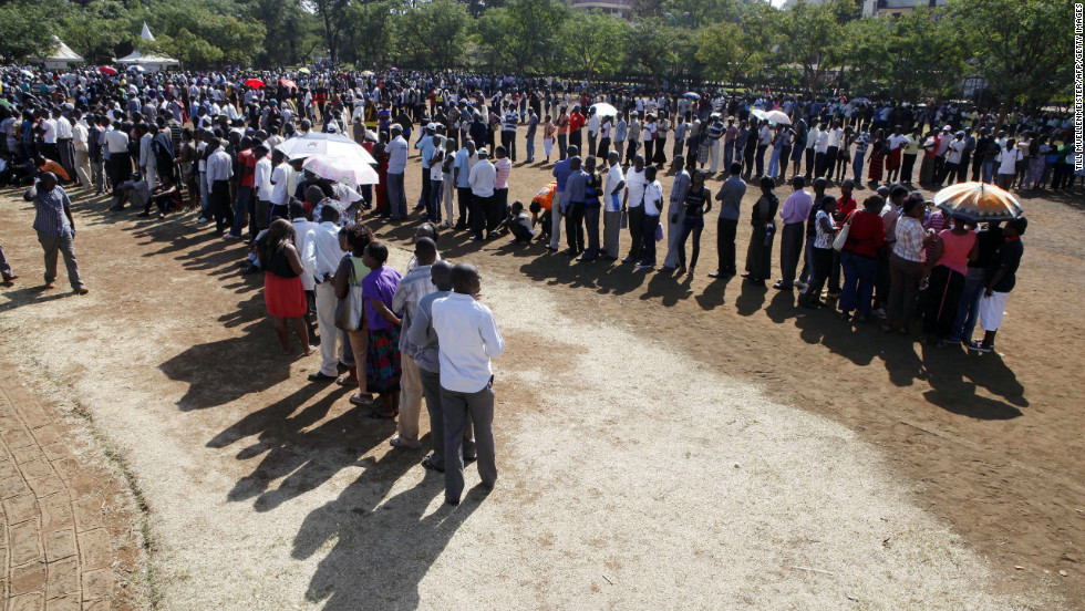 People stand in line to cast their vote at a polling stations in Kisumu, western Kenya on March 4, 2013 during the nationwide elections.