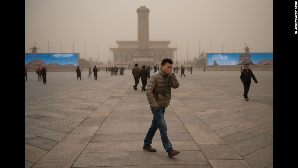 A man covers his face as he walks around Tiananmen Square during a sand storm in heavily polluted weather in Beijing on February 28.