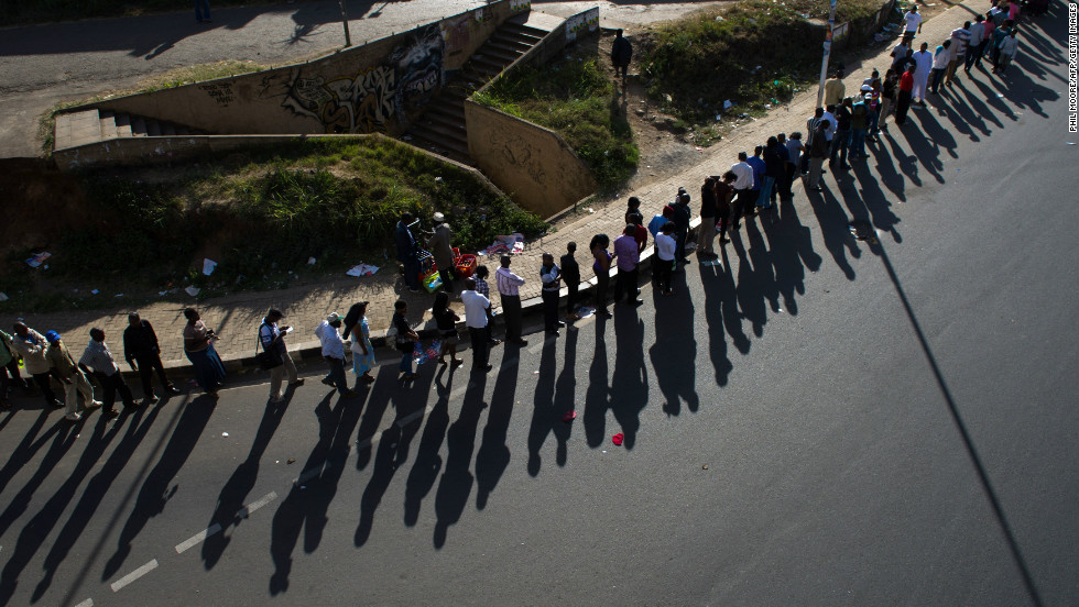 Shadows of a long queue of voters is cast upon the road, just before voting is due to close, in downtown Nairobi, the Kenyan capital, on March 4, 2013 as Kenyans vote in general elections.