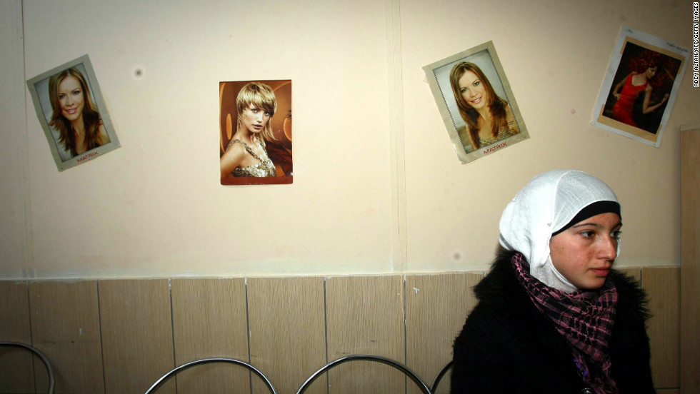 In November 2012, a Syrian refugee waits at a hairdresser's shop inside the Oncupinar camp in Kilis, Turkey.