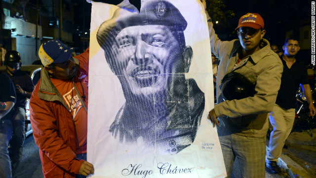 Supporters of Venezuelan President Hugo Chavez hold an allusive poster while gathering in front of the Military Hospital in Caracas on March 5, 2013, after knowing of their leader's death. Chavez lost his battle with cancer, silencing the leading voice of the Latin American left and plunging his divided oil-rich nation into an uncertain future.