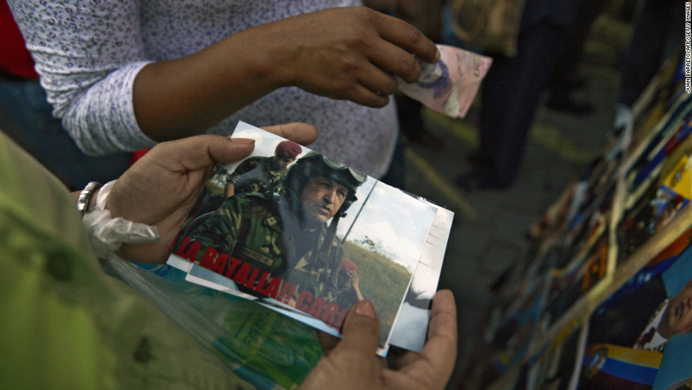 Chavez supporters hold pictures of the late president as they gather on March 5 in front of the Military Hospital in Caracas.
