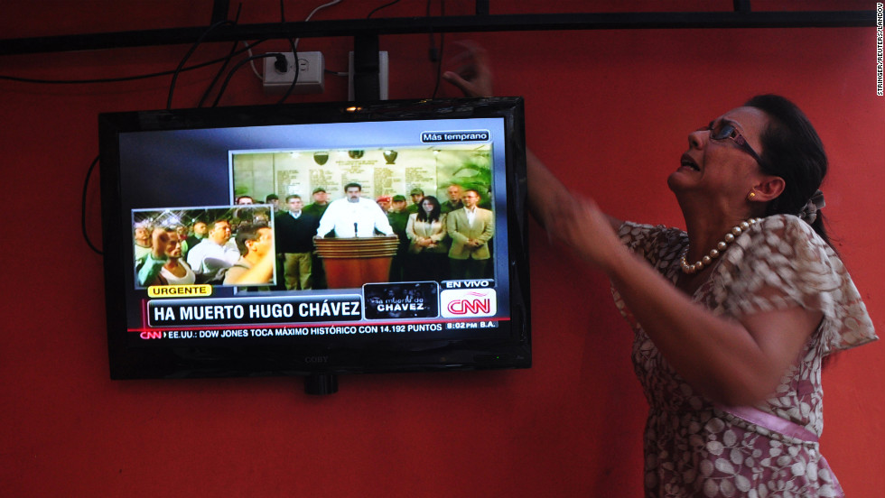 A Venezuelan woman adjusts the television while watching the news of Chavez's death on March 5 inside a Venezuelan restaurant in Panama City, Panama.