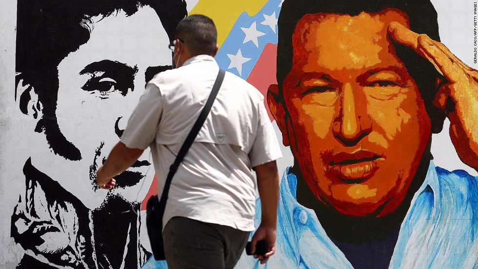 A man walks past a mural in Caracas portraying the South American liberator Simon Bolivar, the Venezuelan flag and Chavez on March 5.