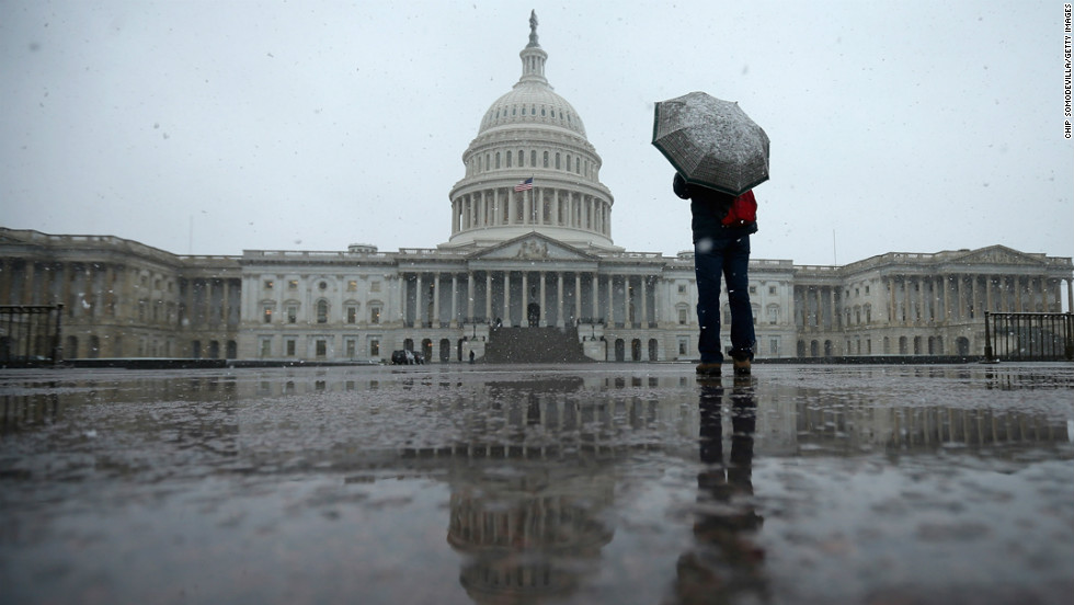 A tourist takes cover under an umbrella while snapping photos of the U.S. Capitol on March 6, in Washington.